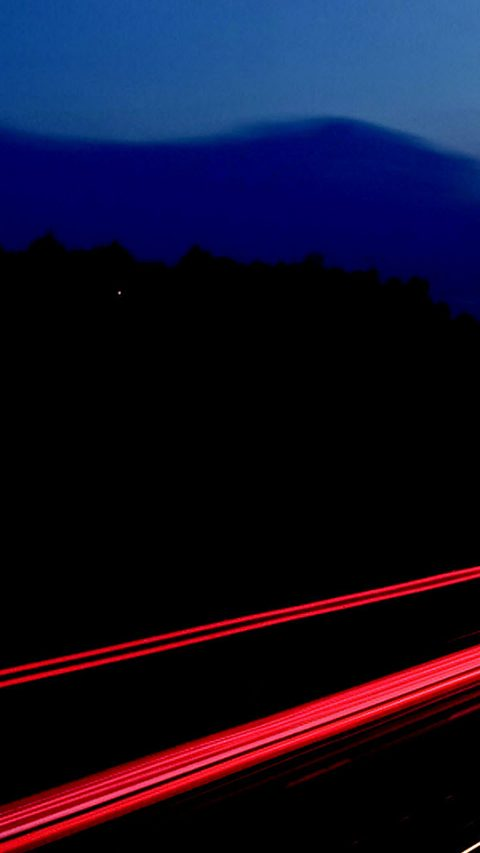 long exposed image of highway at night with red and yellow lines