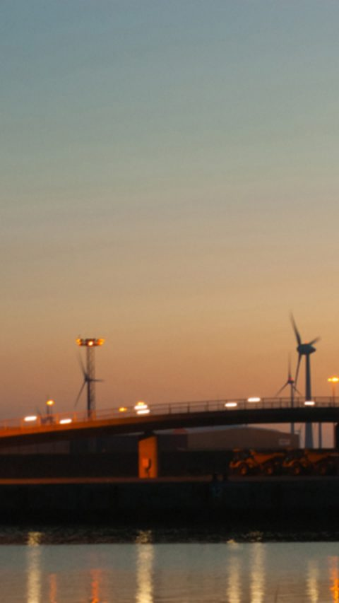 Landscape view of a bridge by the water with windmills during sunset