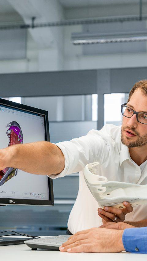 Ein neues Konzeptauto – gemeinsam entwickelt von BASF und Hyundai Motor Company – vereint innovative Lösungen der Chemieindustrie mit zweckmäßigem aerodynamischen Design und spezifischen Hochleistungstechnologien. Die Gestaltung eines Kunststoffbauteils lässt sich durch moderne digitale Methoden noch vor dem Werkzeugbau deutlich verbessern und beschleunigen. Anhand eines digitalen Modells auf dem Bildschirm und des korrespondierenden 3D gedruckten massstäblich verkleinerten 3D Druckmodells diskutieren die beteiligten Ingenieure Sebastian Ebli (links) und Andreas Wüst (rechts) den Kraftfluss im Sitz des Concept Cars.