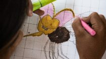 Child colorizes a mosquito drawing